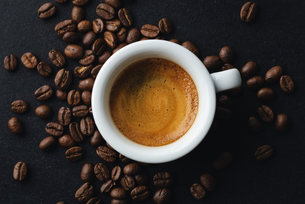 steaming espresso in cup with coffee beans