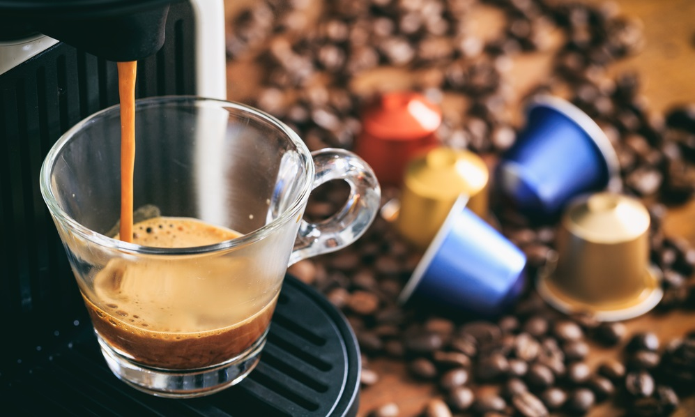 Espresso coffee maker and capsules on a wooden table